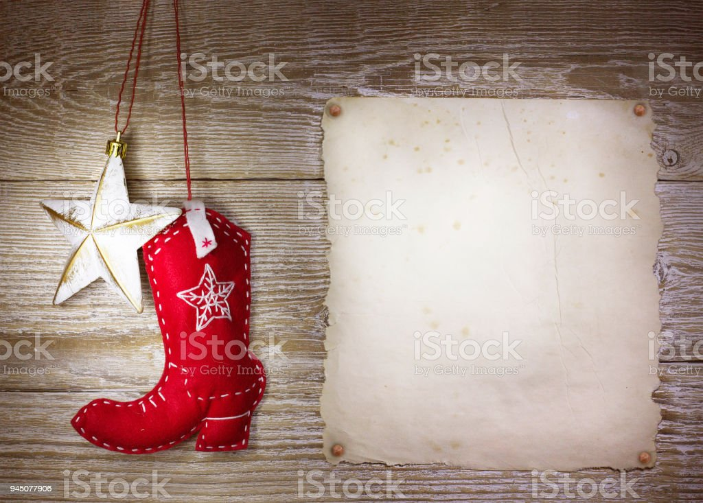 Cowboy christmas background with western toys boot and star on old paper texture stock photo
