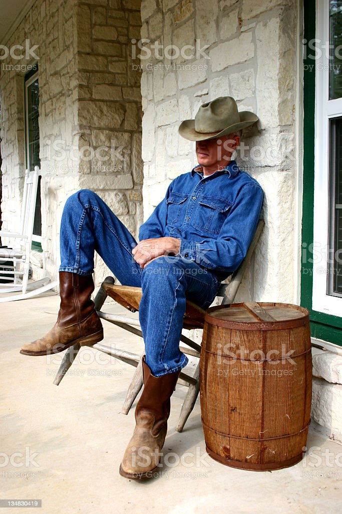 Cowboy dozing in old chair on porch nail keg table royalty-free stock photo