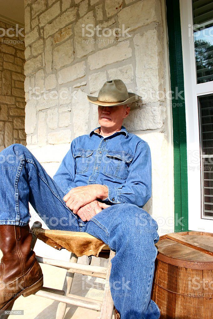 Cowboy dozing on porch royalty-free stock photo