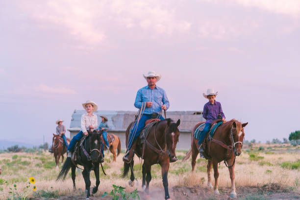 Cowboy father and sons at sunset Cowboy father and sons at sunset. Utah, America. August 2017 rancher stock pictures, royalty-free photos & images