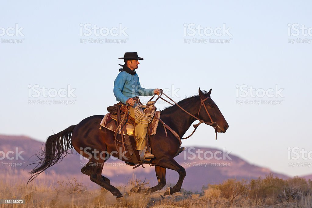 Cowboy gallops by as horse is completely off the ground stock photo