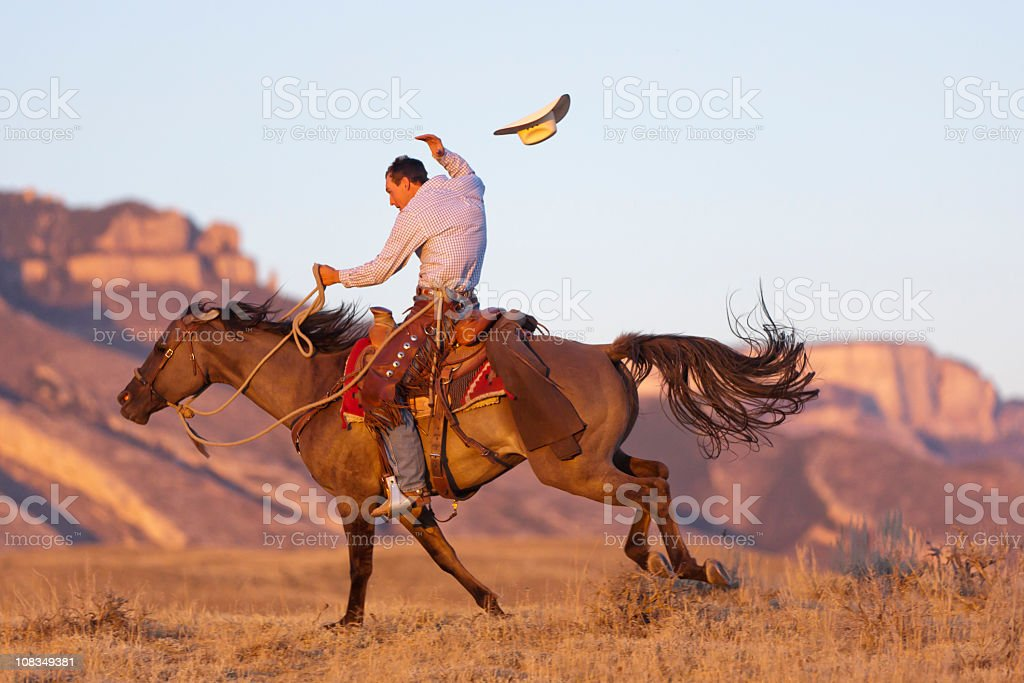 Cowboy gallops by on horse and loses hat stock photo
