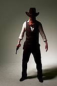 A mysterious cowboy gunslinger against an off white grungy stippled background