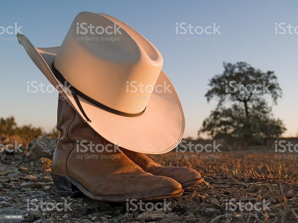 Sombrero de vaquero y fundas en una puesta de sol - foto de stock
