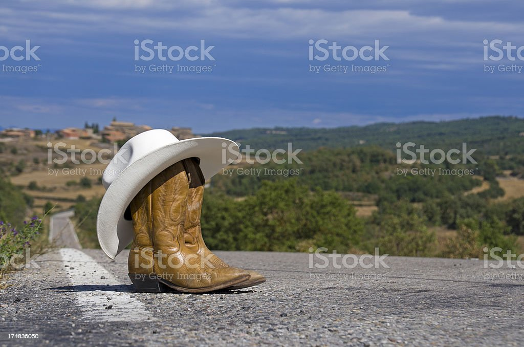 Cowboy hat and boots in the middle of a road royalty-free stock photo