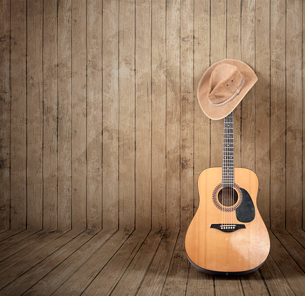 Cowboy hat and guitar Cowboy hat and guitar against a wooden background. country and western music stock pictures, royalty-free photos & images