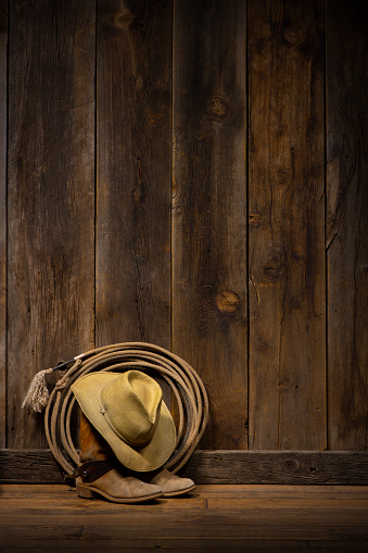 Wild West theme with a barn wood wall and floor with cowboy boots with spurs, hat and lasso. Most of the image is barn wood wall with large area for copy space.