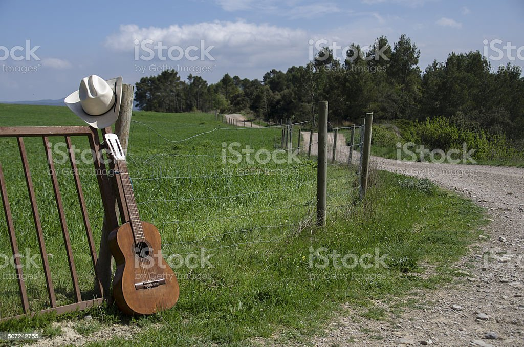 Sombrero de vaquero, guitarra y valla - foto de stock