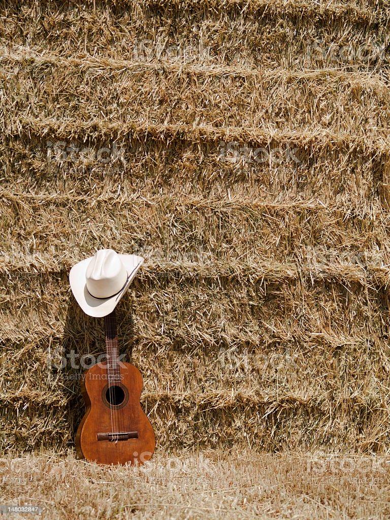 Sombrero de vaquero, guitarra y hay - foto de stock