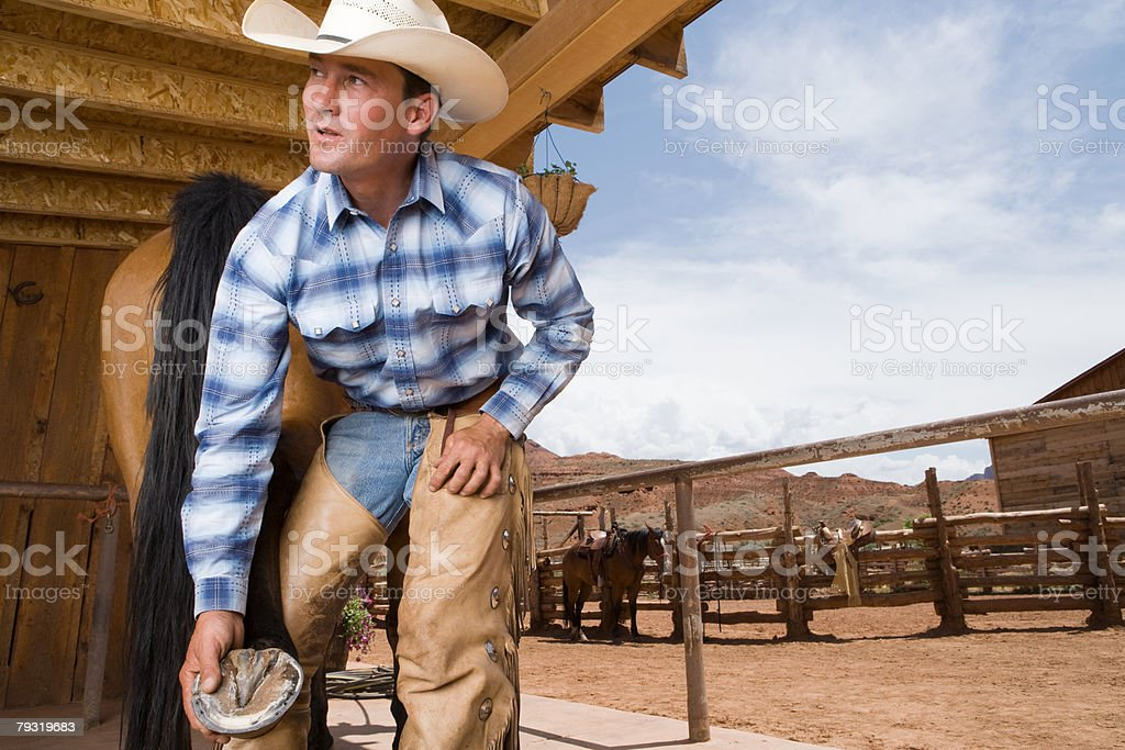 Cowboy holding horse hoof royalty-free stock photo