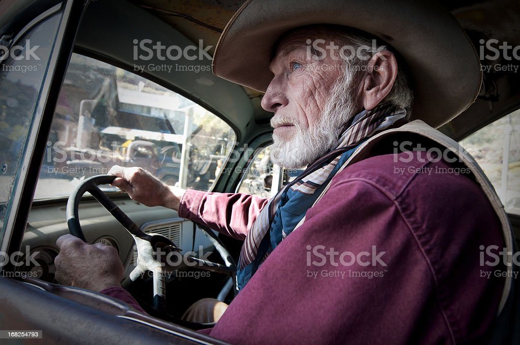 Cowboy in an old truck stock photo