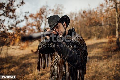 One man, young cowboy with a shotgun, aiming to shot.