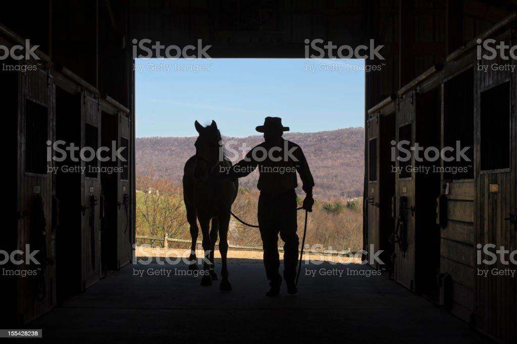 Cowboy Leading Horse Silhouette in Barn Door, Summer Mountain La stock photo