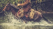 Side view of a cowboy riding his horse across a river in a forest.