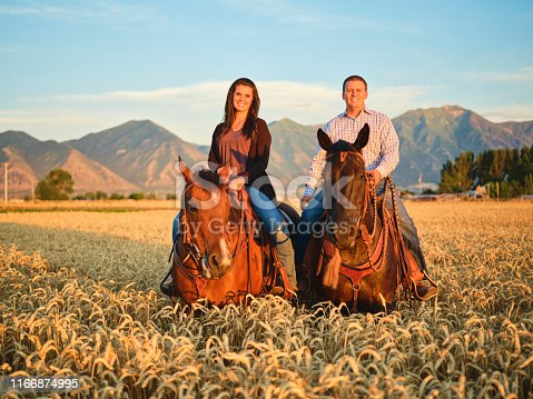 A cowboy couple on their horses on a ranch in Utah, USA.