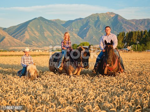 A cowboy family on their horses on a ranch in Utah, USA.