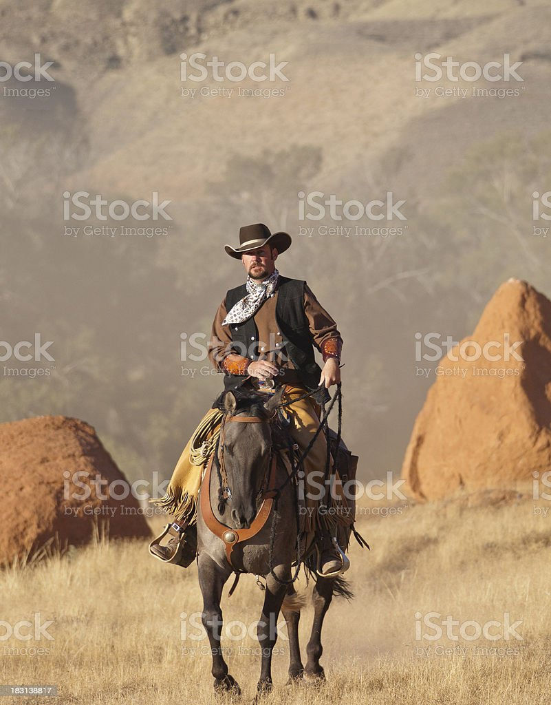 Cowboy rides horse between two large boulders stock photo