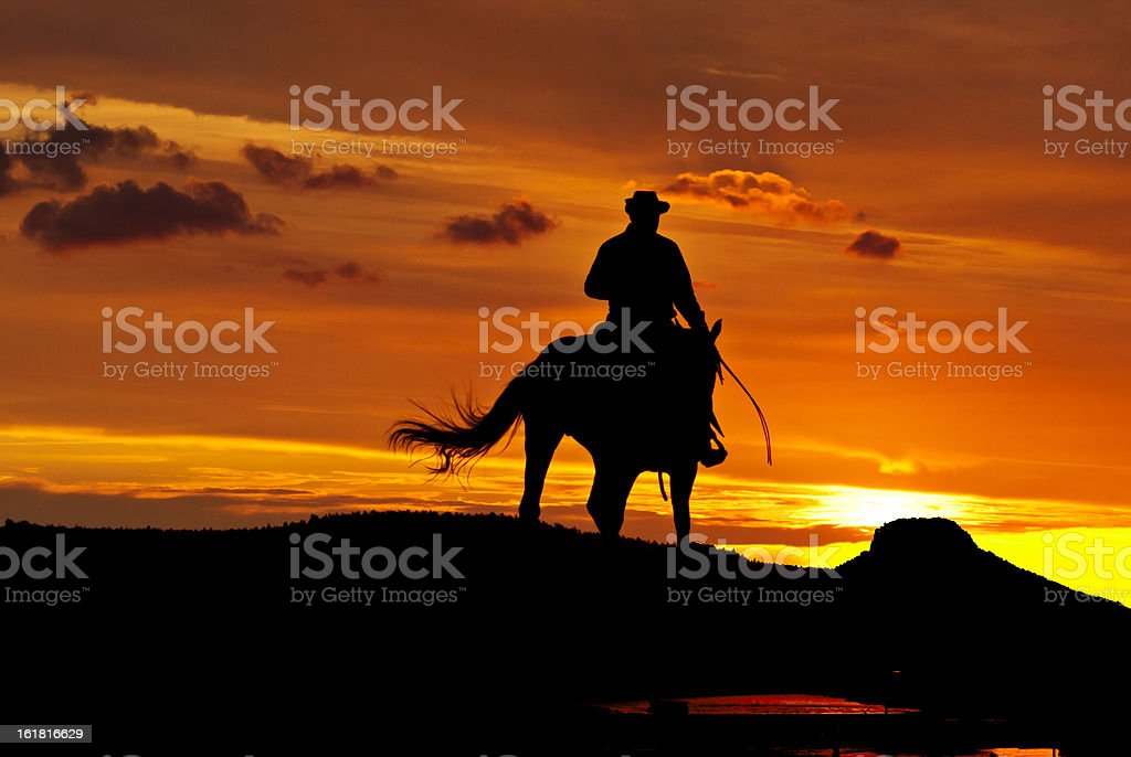 Cowboy rides into the night stock photo