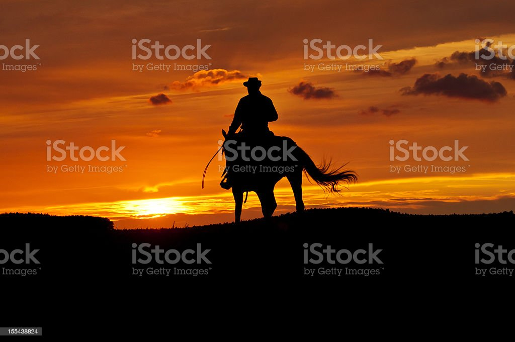 Cowboy rides into the sunset stock photo