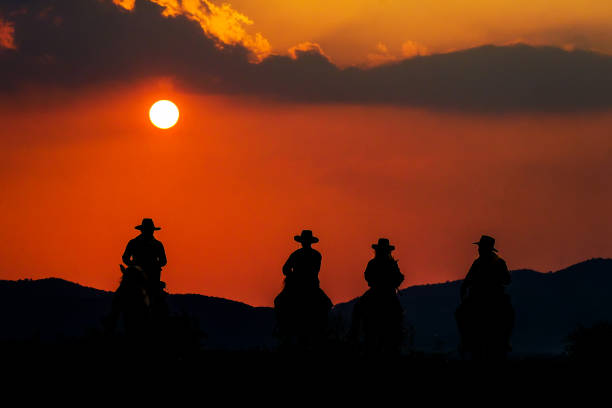Cowboy riding a horse near the sun