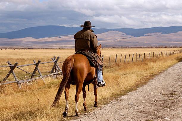 A cowboy riding a horse on a dirt trail stock photo