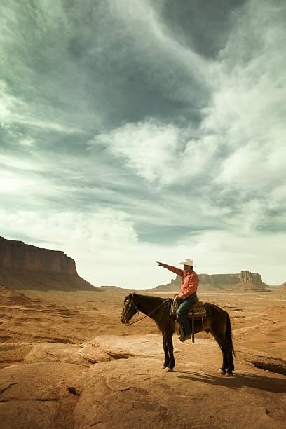 cowboy auf einem pferd zeigt die richtung des amerikanischen südwestens - navajo stil stock-fotos und bilder