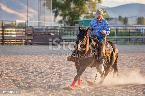 Mature Cowboy riding his horse inside Rodeo Arena in Sunset Light. Wild West USA Rodeo Series. Spanish Fork, Salt Lake City, Utah, USA