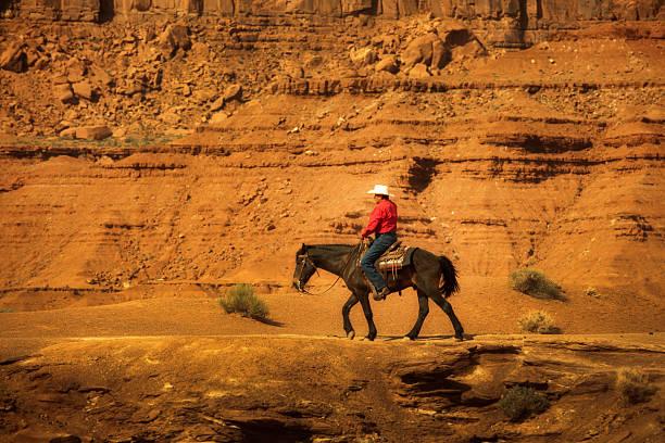 cowboy auf pferd auf navajo land im amerikanischen südwestens - navajo stil stock-fotos und bilder