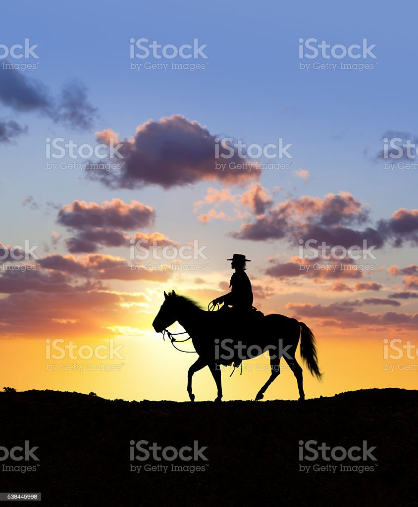 Cowboy riding lonely through the wilderness at sunset stock photo