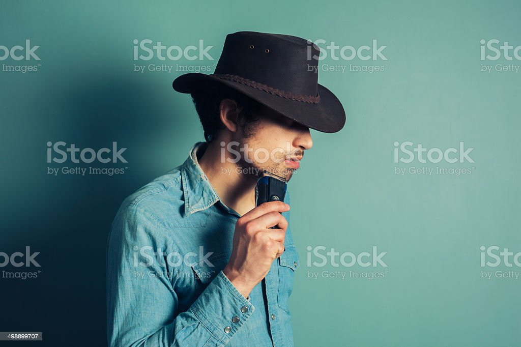 Cowboy shaving with electric shaver stock photo