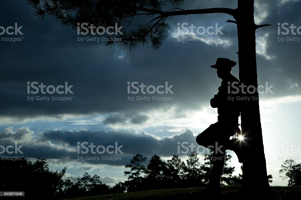 Cowboy: Silhouette rancher, farmer overlooking field after rainstorm at sunset. stock photo