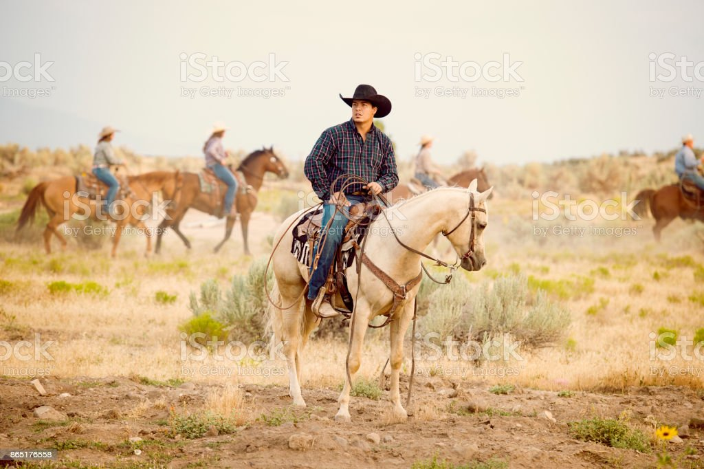 Cowboy Sitting Astride His Beautiful Palomino Horse Others Riders Passing By In The Background Stock Photo Download Image Now Istock