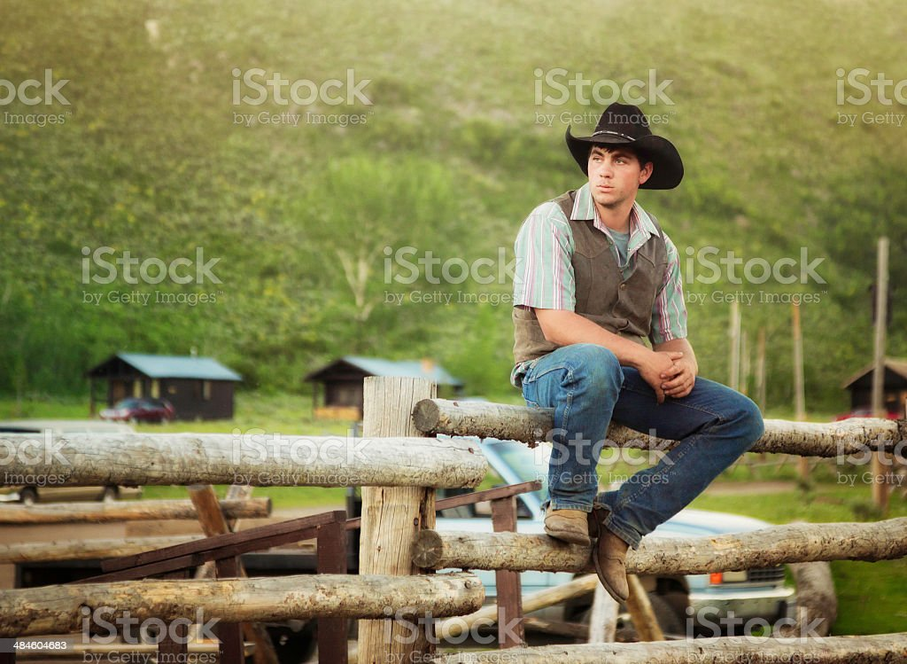 Cowboy sitting on log fence at ranch in Montana USA stock photo