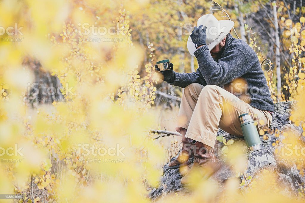 Cowboy sitting on rock in the woods of Montana stock photo