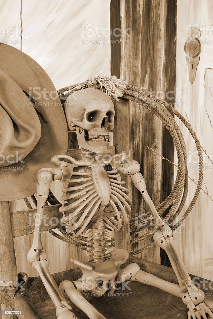Cowboy skeleton sitting in chair, he died waiting, sepia tone royalty-free stock photo