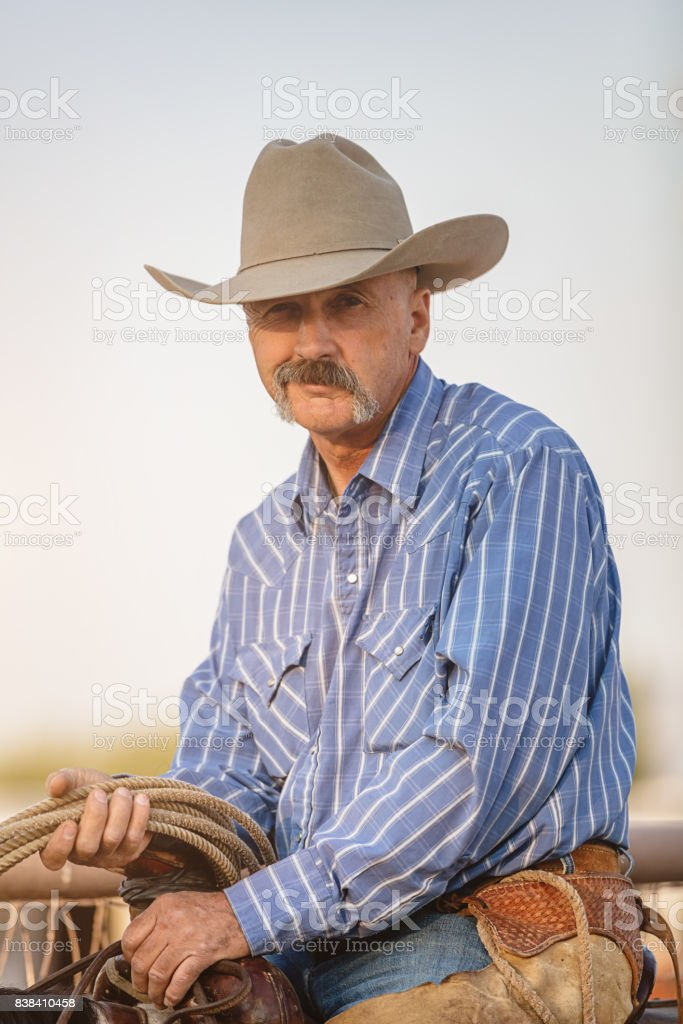 Cowboy sitting on his horse with a sneering naughty and skeptical...