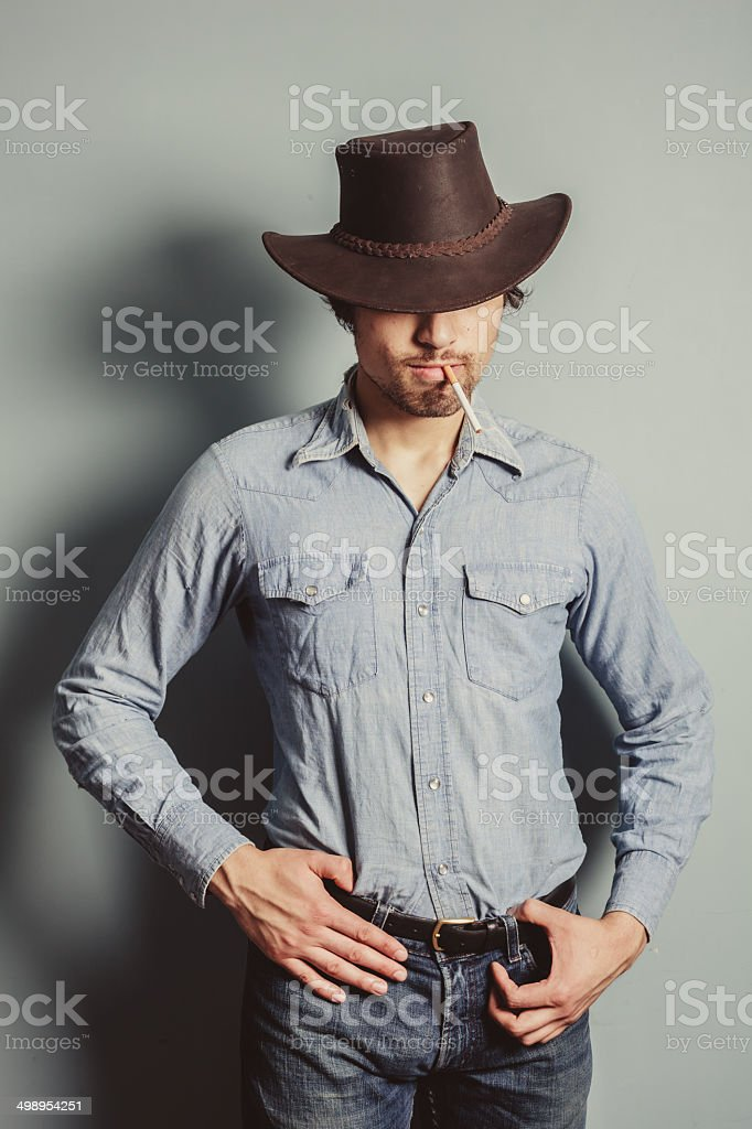 Cowboy standing by a blue wall smoking cigarette stock photo