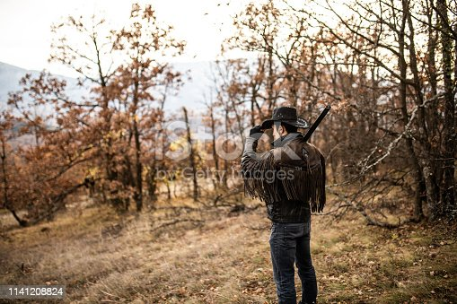 Rear view with cowboy holding hat and rifle on his shoulder, outdoor