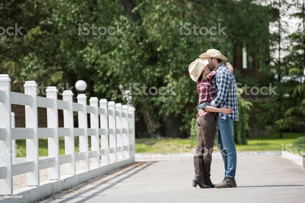 cowboy style couple kissing while spending time in park at daytime stock photo