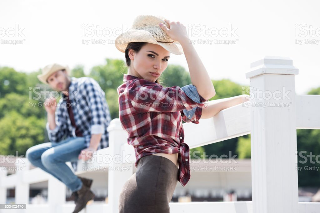cowboy style girl posing and looking at camera near fence on ranch stock photo