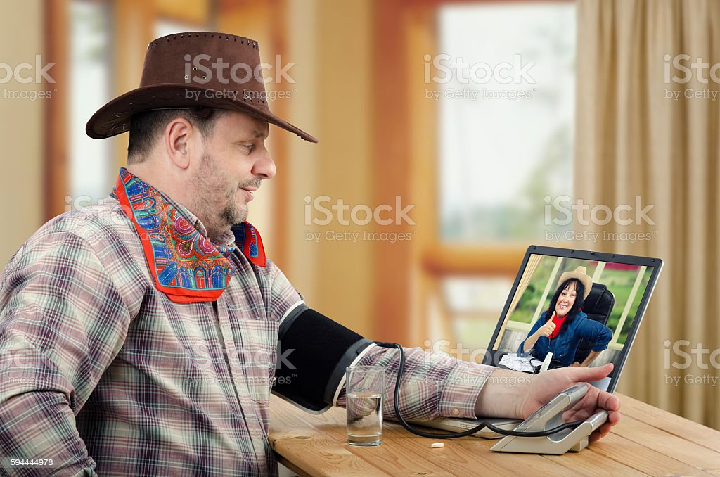 Cowboy takes his own blood pressure online stock photo