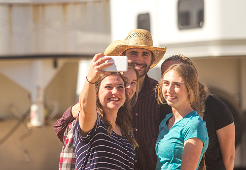 cowboy taking selfie with young farmer girl  friends at ranch paddock in Salt lake City SLC Utah US