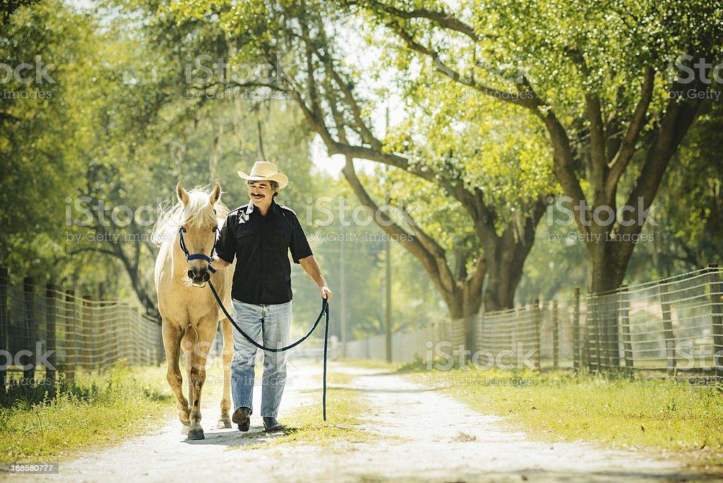 Cowboy walking a horse stock photo
