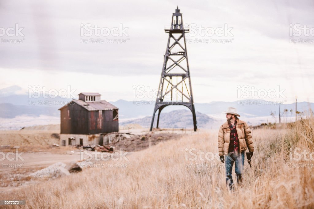 Cowboy walking through field with oil drill and barn royalty-free stock photo