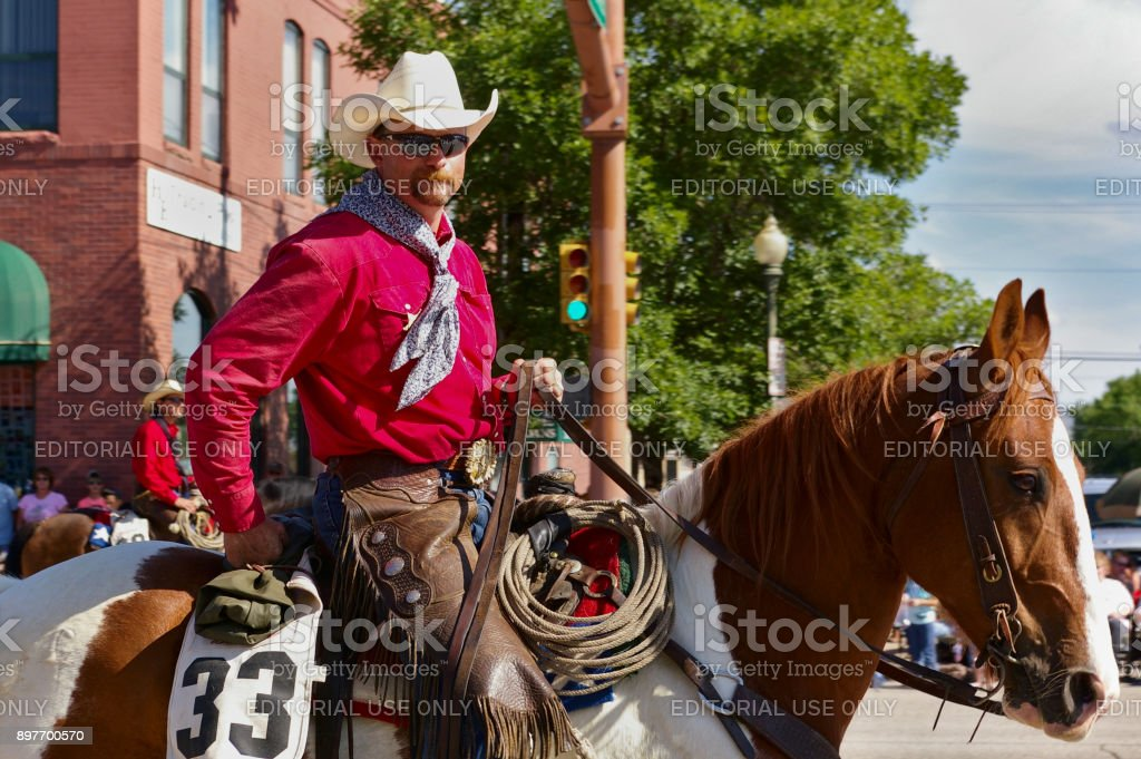Cowboy with bright red shirt riding on the Independence Day Parade stock photo