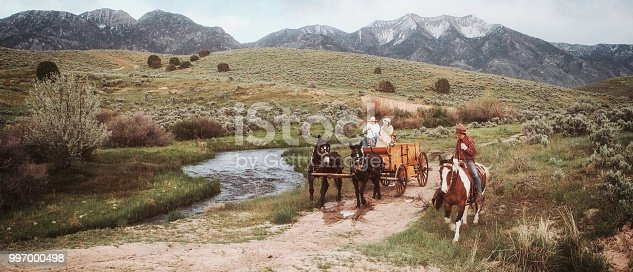 A group of cowboys and cowgirls riding horses in the desert wilderness of Utah, USA.
