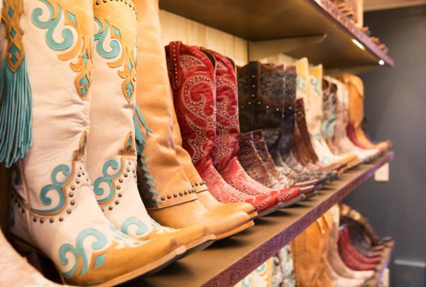 cowboys-stiefeln auf einem regal in einem geschäft ausgerichtet - houston texas stock-fotos und bilder