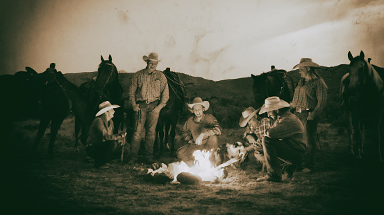 Cowboys and Cowgirls outdoors around the campfire in the west.