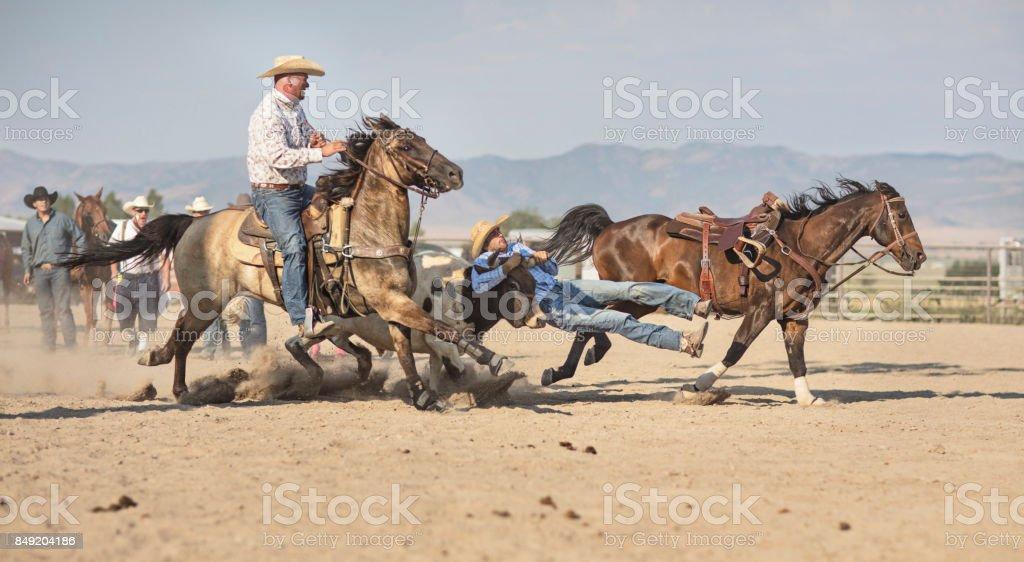 Cowboys chasing Bull at rodeo riding action in Utah, USA stock photo
