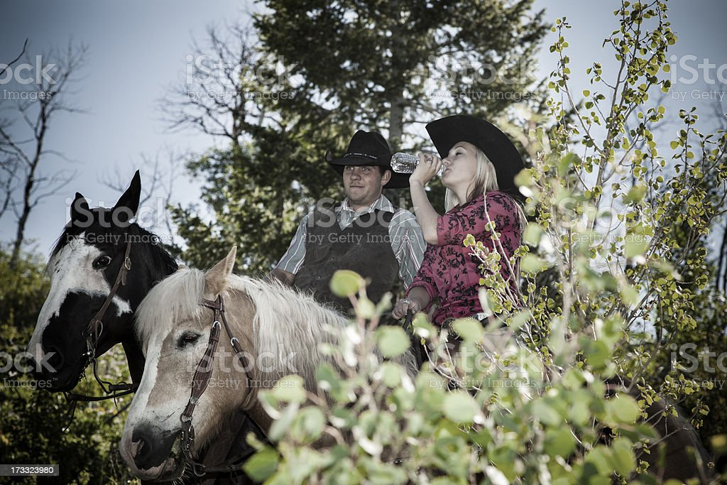 Cowboys: Couple riding horses together on trail. Woman drinks water. royalty-free stock photo